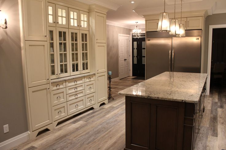 August 2015 #kitchen #renovation featuring cabinets from Deslauriers Custom Cabinets, cherry wood with Englefield door style, elegant two-tone design, built-in over the range hood detailed to match cabinets, a Rubinet pot filler over the stove, large island with 1¼ thick granite, built-in counter depth double door fridge and freezer (built-ins also include a decorative buffet and hutch with glass front doors and Richelieu crystal knobs and pulls), and @hinkleylighting chandelier + wall…