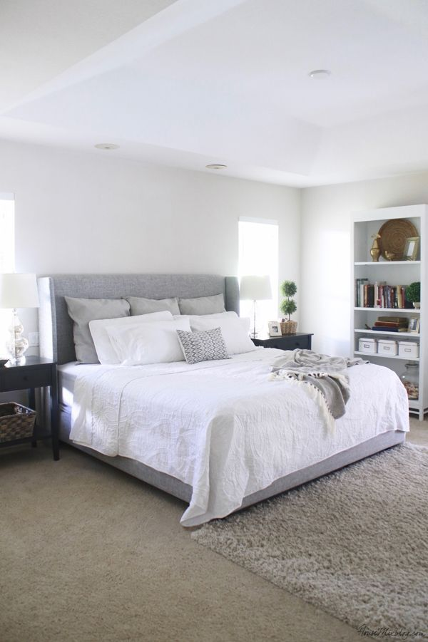 White bedroom with gray upholstered bed and large black ...