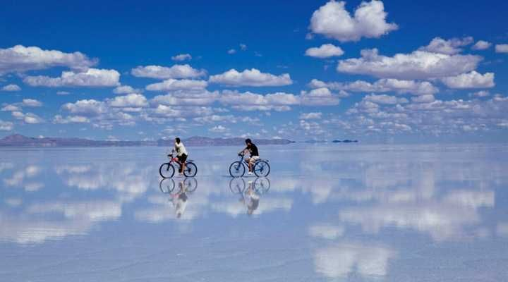Salar de Uyuni, BOLIVIA. Unreal as it looks, Salar de Uyuni is just a huge saline flat. The shallow pool of brine transforms the salt pan into a gigantic mirror. It reflects the cerulean blue above creating the effect of an endless sky in which people walk and cars drive as if gravity laws did not exist.
