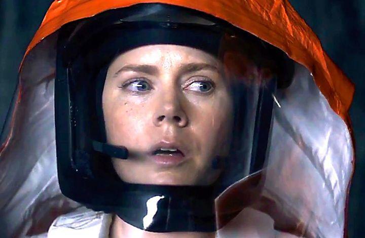 Arrival's Amy Adams in hazmat suit looks intensely to her left