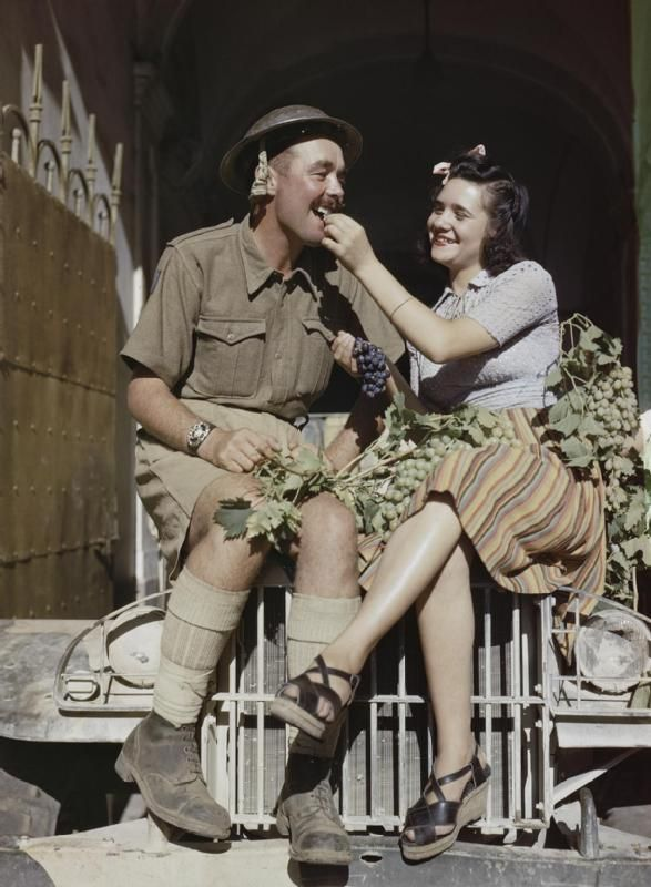An Eighth Army British soldier enjoys being fed grapes by a local girl in Sicily - August 1943.