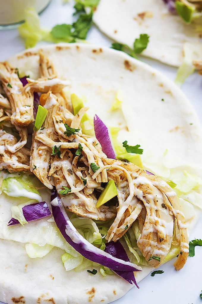 Slow Cooker Ranch Chicken Tacos - Slow cooked ranch chicken wrapped in soft flour tortillas and topped with red onion and cabbage slaw and ranch dressing!