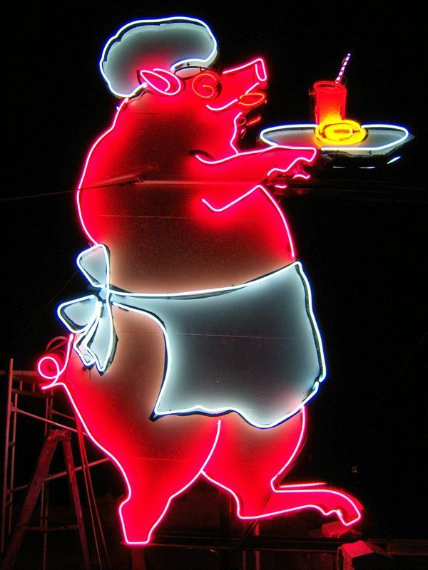 A NEON PIG WAITING ON TABLES.