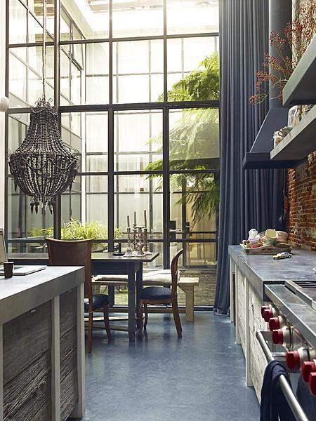 """Industrial Kitchen"": A 2-story window wall provides dramatic views and light for this loft kitchen. Salvaged wood from a demolished barn is used for the cabinetry, while the dining room is highlighted with a clay bead chandelier and full height curtain. 
