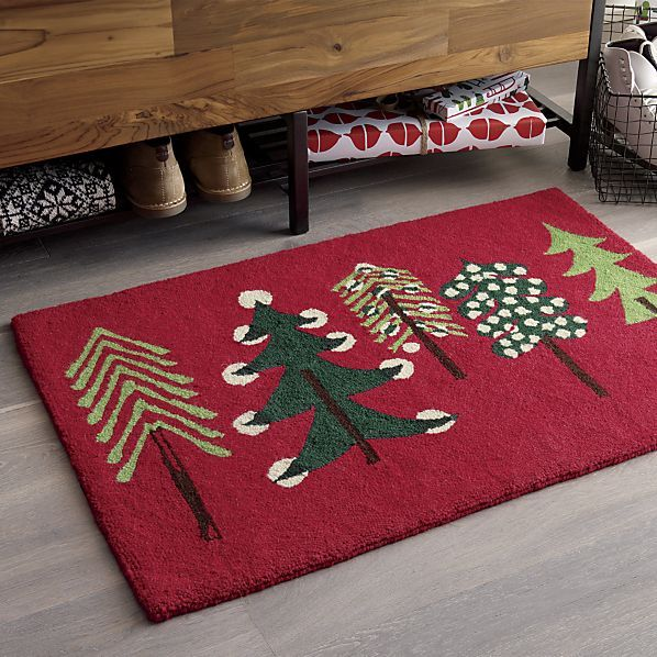 Designer Jenny Bowers takes a fresh approach to a traditional holiday theme in the whimsical firs and pines that blanket this red doormat in fresh, tonal greens.