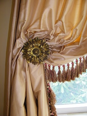 lush apricot silk drapery panel over gilded holdback with tassels