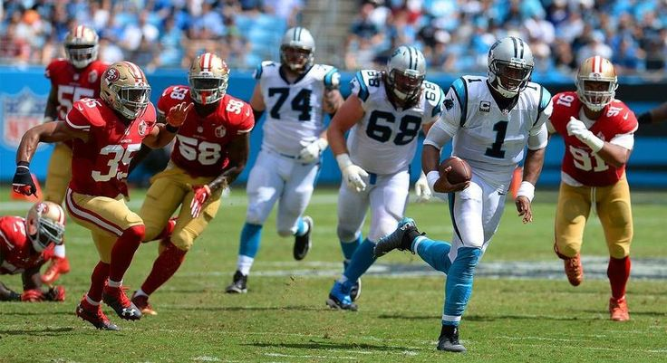 Carolina Panthers quarterback Cam Newton, right, rushes for yardage against the…
