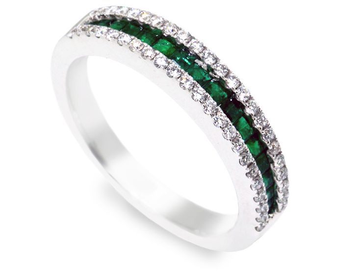 This diamond and emerald wedding band is made in 18 karat white gold.