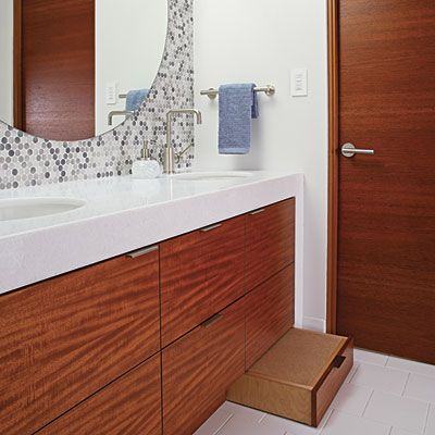 "Instead of lowering the vanity so kids can reach, keep it at the standard height and incorporate a stool in the toe kick that can be pulled out when needed so you aren't constantly tripping over it. ""If the family really wants a lower vanity, I suggest doing a split-height vanity at 33 or 34 inches high—a little lower than average so that adults have to stoop a bit and kids have to reach a bit for a happy medium,"" advises interior designer Terrell Goeke."