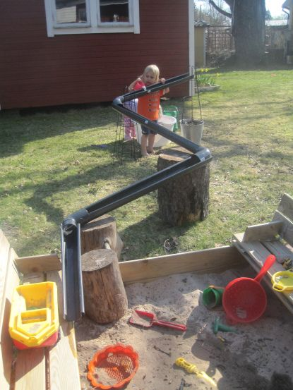 I like the use of the tree stumps with the gutters. Water play or racing cars