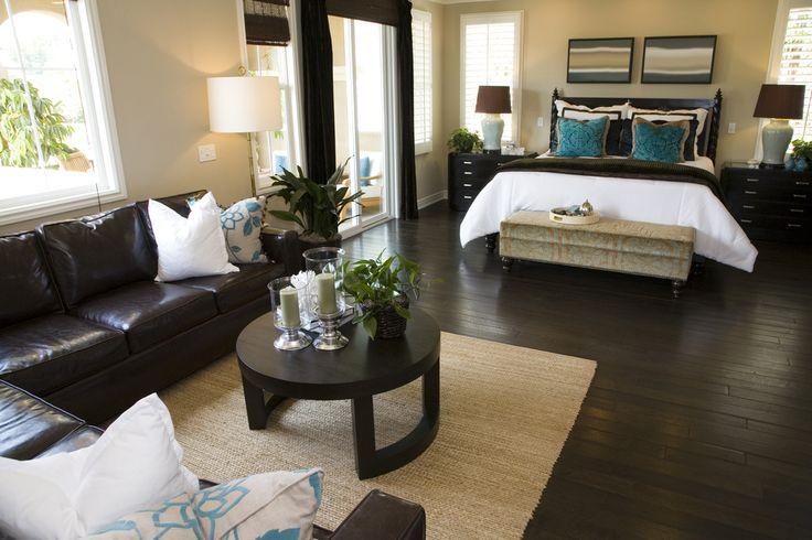 Dormitorio con duro suelo de color marrón oscuro y los muebles, lo que contrasta con puerta de color blanco y ventanas.