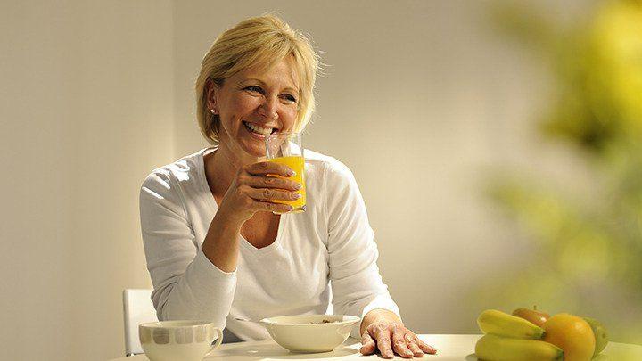 older woman eating breakfast foot