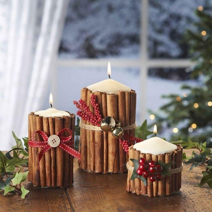 bougies blanches décorées de bâtons de cannelle et rubans rouges