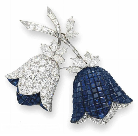 """A """"mystery-set"""" sapphire and diamond flower brooch by Van Cleef & Arpels. Two calibré-cut sapphire and circular-cut diamond flower blossoms, with baguette and marquise-cut diamond accents.  Baguette-cut diamond stems and marquise-cut diamond leaves.  All mounted in platinum and 18k gold.  French assay marks, 1967"""