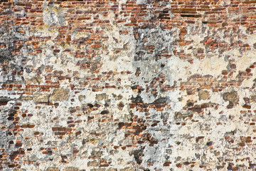 Old italian stone and brick wall with degraded plaster