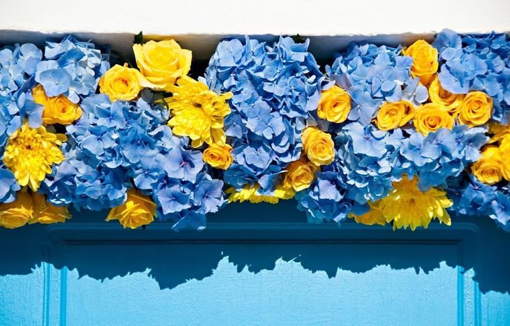 When Brazil Meets Greece Wedding @ Alemagou, Mykonos by De Plan V. Church's main entrance garland decoration with vibrant yellow roses, chrysanthemums and hydrangeas in cobalt blue!
