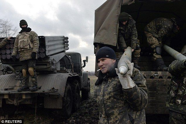 Pro-Kiev forces unload Grad rockets from a truck before launching them towards pro-Russian...