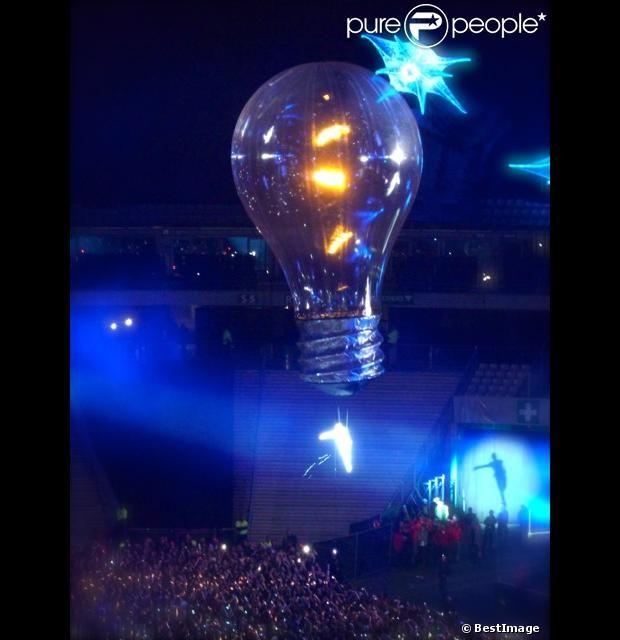 Une acrobate survole le stade perchée sous une ampoule géante pendant le concert de Muse au Stade de France le 21 juin 2013.