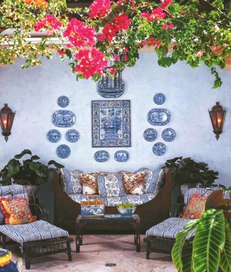A tiled mural is accented with more blue and white, in a symmetrical display using plates and platters.: