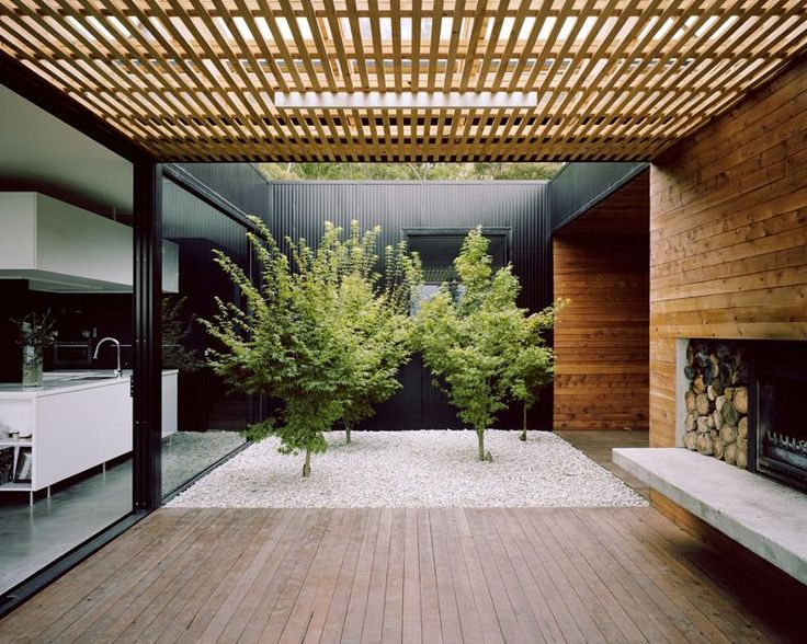 Courtyard at centre of house. Carport to right, kitchen to left, outdoor room with fireplace Dark walls Burnished concrete floor Timber wall cladding Room 11 Architects
