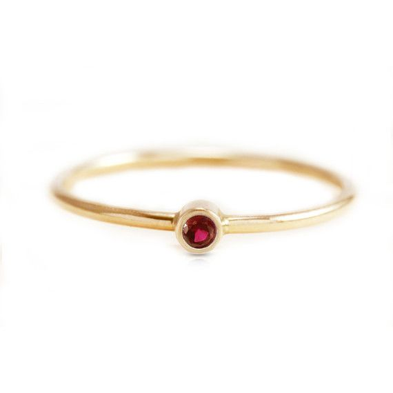 Simple and delicate ruby red ring in 14k yellow gold. Stacks well with other rings; also available in emerald, blue sapphire and diamond. Additional Details: • Bezel-set: 2mm natural ruby • Ultra thin