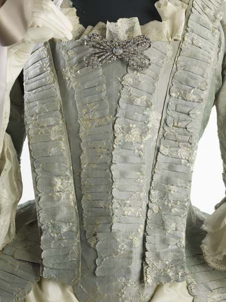 Bodice detail of 1760s gown made from very fine silk (lustring). The small flower pattern in off-white woven into the pale blue background suggests a date of around 1755 for the fabric, though the gown was made possibly a decade later. Museum of London