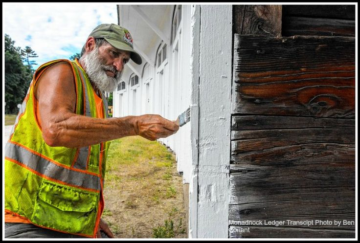 Tim Chapman, from Hancock's DPW, paints the curving horse sheds behind the Hancock Meetinghouse. The horse sheds are on the cover of Sheds by Howard Mansfield.   #New England, #Barns, #Architecture, #Historic Preservation, #Tiny Houses, #Horse Sheds, #Covered Bridges, #A Frames, #Quonset, #Barns, #Saunas