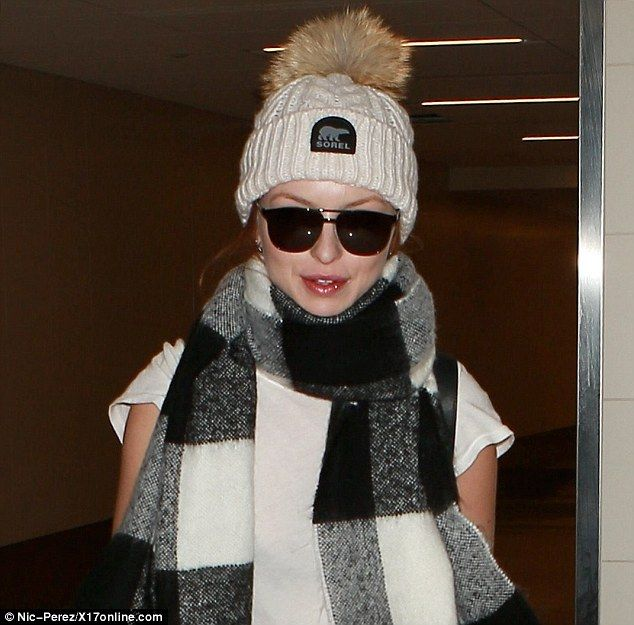 Less is more:Scooping her hair up into a casual bun, she seemed to be make-up free for the flight back to LA