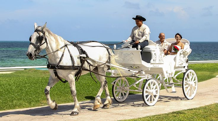 Bride Marta and her father ride along the Caribbean in a Cinderella carriage on their way to the wedding ceremony at Moon Palace Cancun #destinationwedding