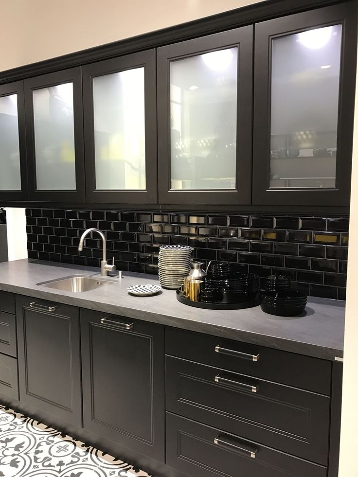 Black kitchen cabinets with subway tiles and white frosted ...