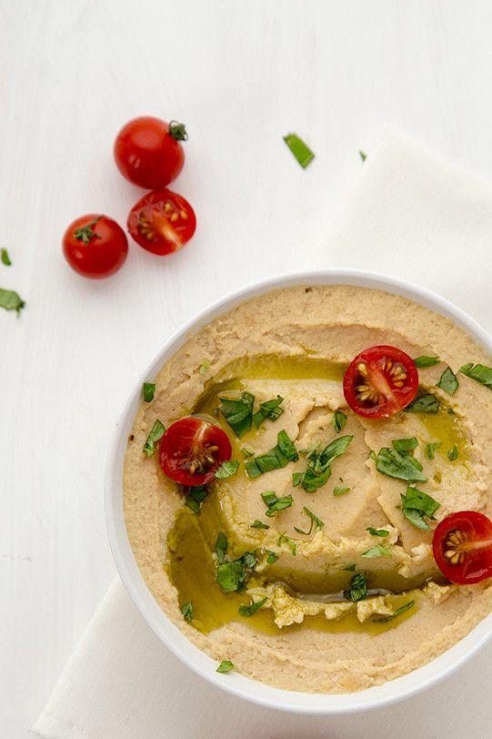 炒めにんにくのフムス       ひよこ豆たっぷりのヘルシーなパテ なお(直宏)    材料 (6人分)   茹でたひよこ豆 260g(2カップ)   白ごまペースト 大さじ2と1/2   レモン汁 大さじ2   オリーブオイル 大さじ2   にんにく ふたかけ   塩、こしょう 少々    作り方   1 にんにくは皮をむき、上下を切り落とし、オリーブオイルで弱火で炒める。軽く色づき柔らかくなるまで。    2 フードプロセッサーにひよこ豆、白ごまペースト、レモン汁、にんにく、オリーブオイルを入れ、しっかり撹拌する。    3 お好みでひよこ豆の茹で汁を加えてさらに粉砕し、滑らかさを調節する。    4 塩とこしょうで味をととのえる。   コツ・ポイント   白ごまペーストやレモン汁と合わせることで、ひよこ豆のちょっとくせのあるフレイバーが隠れるのがいいなと思います。クラッカーなどに乗せて、サンドイッチの具にして、たのしんでみてくださいね。    レシピの生い立ち…