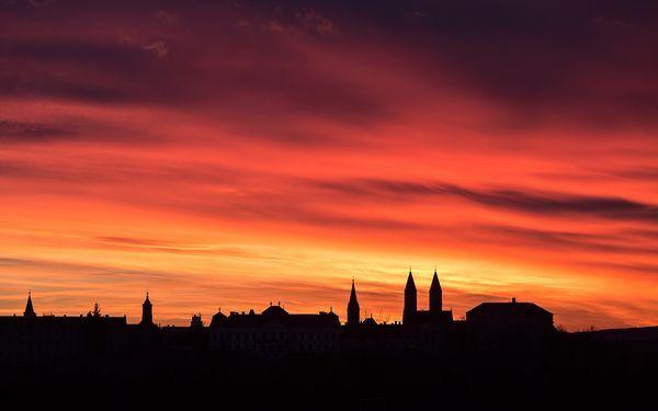 Cielo in fiamme Fotografia di Tamas Ladanyi, TWAN  Il sole al tramonto accende il cielo sulla cattedrale di San Michele (le due torri sulla destra) a Veszprém, in Ungheria. Il fotografo ha catturato questi colori brillanti su pellicola, durante il solstizio d'inverno.