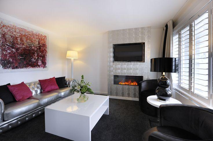 Hotel 's-Hertogenbosch-Vught Waan uzelf in een moderne, romantische omgeving en relax bij de sfeerhaard, in deze Shakespear Suite met afwisselend zilveren en roze tinten. U slaapt op een comfortabele kingsize boxspring. De 51 m2 grootte suite is uitgerust met balkon met een zitje, airconditioning , zitje met een flatscreen tv en sfeerhaard, safe, minibar en koffie & thee faciliteiten. De luxe badkamer is ingericht met een royaal 2-persoons ligbad en een separate inloop regendouche.