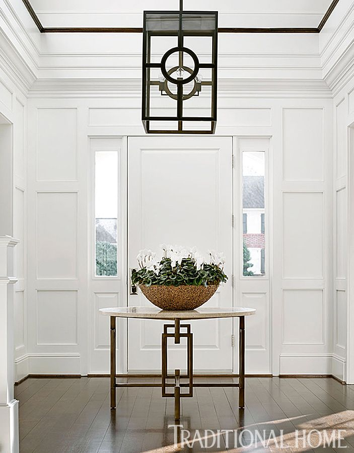 "The house's clean, light, airy quality is established immediately in the entry, arguably the home's most compelling space. ""I created the two-story foyer with paneling to create some grandeur,"" Orrell says. ""They're a young couple, but with serious art and beautiful antiques. I wanted grandeur, but in a clean, relevant way."" The designer played with circles and squares in the space with the Pearson table and a custom Urban Electric hanging lantern."