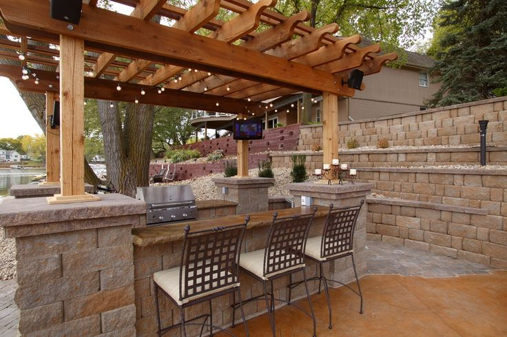An outdoor kitchen complete with countertop seating. Made with the Highland Stone Retaining Wall System