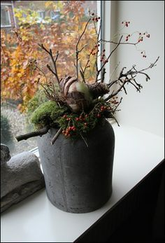 Pot met takken, mos en een grote amaryllisbol.