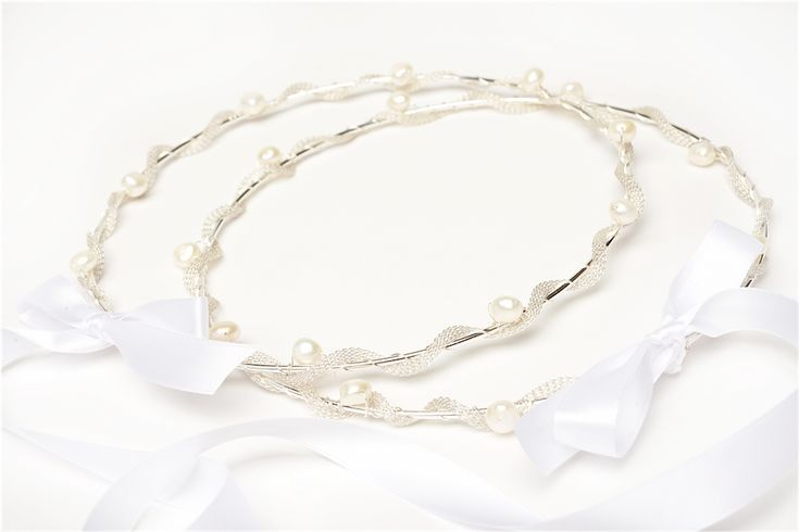These Greek Orthodox wedding crowns feature fresh water pearls, silver plated knitted ribbon around silver plated rings joined with satin ribbon.