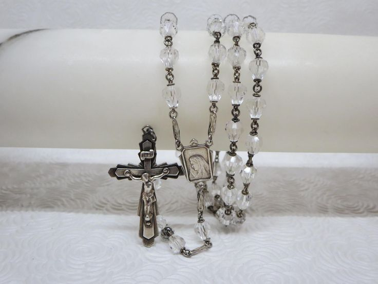 Superb antique Rosary, silver and sparkling beads With hand faceted crystal beads Every 10 beads are separated with a delicately openwork sterling spacer Adorned with a lovely silver center medal of the Virgin Mary Highly collectible!  Very good condition  Size : 21 1/2 inches Weight : 39 g.   ****TODAY DISCOUNT CODE ! VISIT OUR HOME PAGE !*** https://www.etsy.com/ca/shop/LesCurieux?ref=hdr_shop_menu