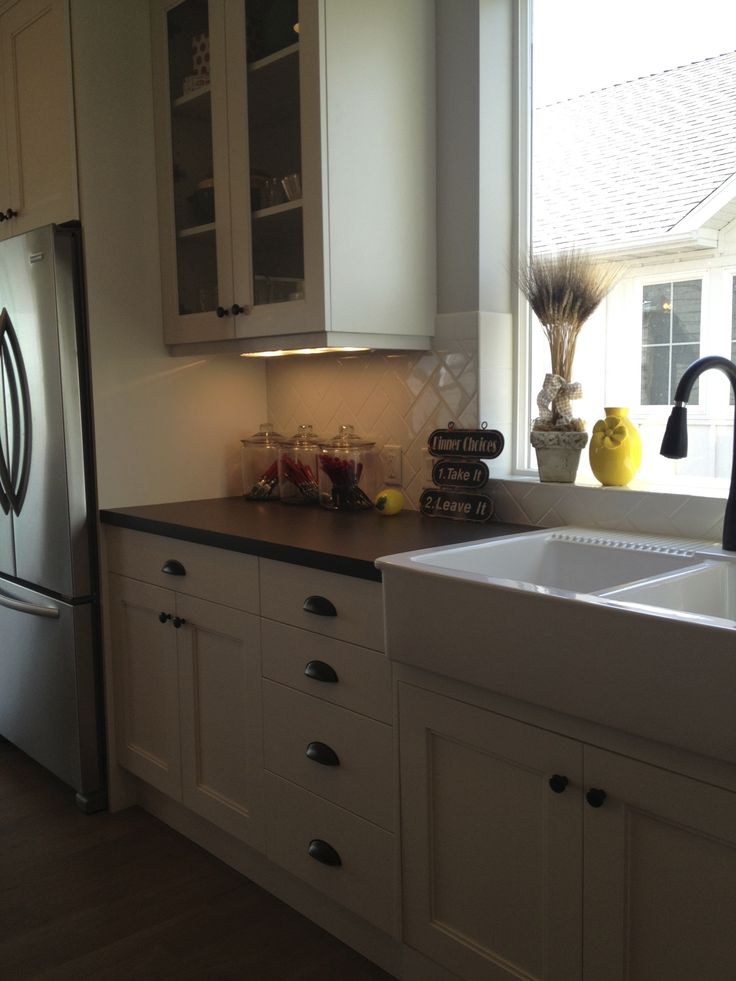 and faucet, white tile backsplash with black granite countertop More