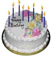 Fancy white birthday cake with pink and yellow decorative flowers and eight burning candles