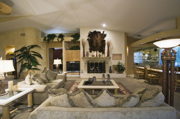 This room features a grey and gold palette, marble fireplace, and full mirror-backed bar on the right.