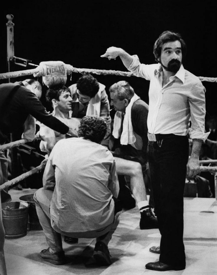 Between takes on the set of Raging Bull, Robert De Niro, Joe Pesci and their fellow cast members have a conversation while Director Martin Scorsese organizes the next shot.