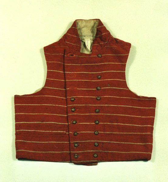 Die rote Herrenweste ist aus einem Wollstoff mit feinen, hellen Seidenstreifen gefertigt. Die Vorderseite zieren achtzehn Filigran-Metallknöpfe in zwei Reihen. Kreis Rendsburg-Eckernförde