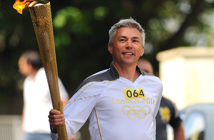 Olympic gold medalist Jonathan Edwards carries the torch through Ilfracombe where he grew up.