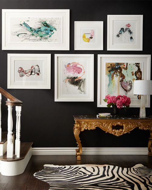 Dark moody foyer walls, bright colored art, wild zebra rug
