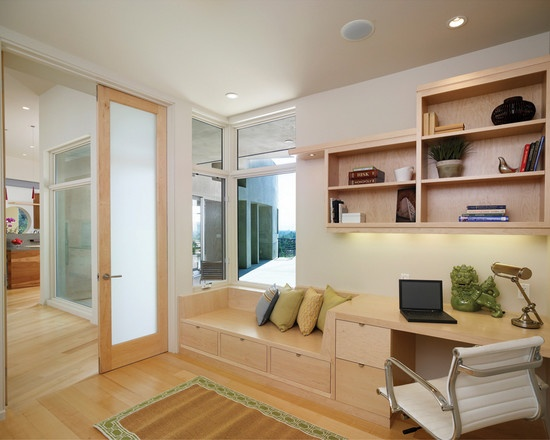 A home office with a bench built into the desk.  Would love to have a book nook in my office.
