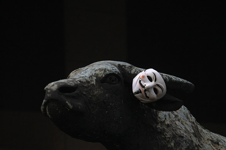 Guy Fawkes Mask hung on the horn of a bronze sculpture outside the Hong Kong stock exchange/Guardian UK