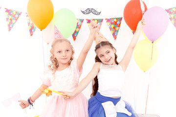 Two pretty little girls during birthday party