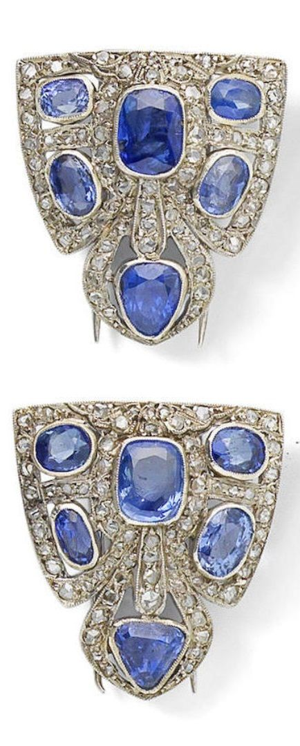 A pair of early Art Deco sapphire and diamond clips, circa 1915. Each shield-shaped clip pierced and set with triangular-cut, cushion, oval and pear-shaped sapphires and rose-cut diamonds, mounted in platinum with millegrain detail throughout, length of each clip 3.2cm. #ArtDeco #clip