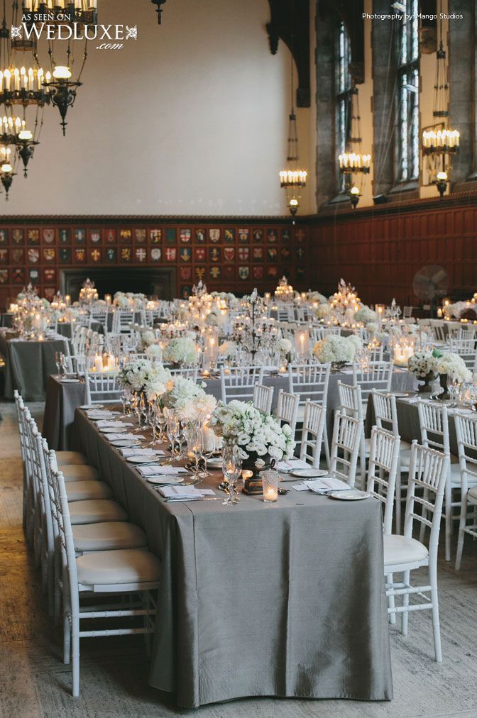 Family style reception with white chiavari chairs, gray table linens, candlelight, white flowersWedLuxe Magazine